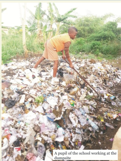 A pupil of the school working at the dumpsite