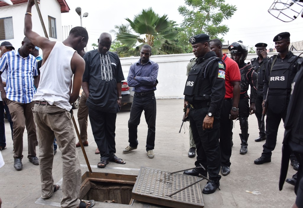 Commander, Rapid Response Squad (RRS), ACP. Tunji Disu (right), is confirming the availability of PMS in the reservoir of a filling Station after denying sales to the public during the arrest of the Manager and Staff of the Filling Station for hoarding Premium Motor Spirit (PMS) in Lagos, on Tuesday, April 05, 2016.
