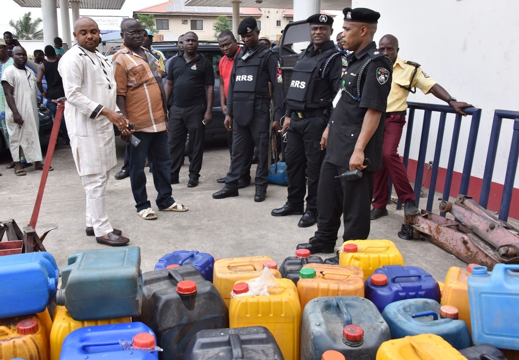 Commander, Rapid Response Squad (RRS), ACP. Tunji Disu (2nd right); Divisional Police Officer, Isheri Police Station, Superintendent Olohunwa Ogundele (right), arresting the Manager and a Staff of a Filling Station for hoarding Premium Motor Spirit (PMS) at Otedola/Omole along Lagos-Ibadan Expressway, on Tuesday, April 05, 2016.